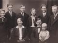 Gårdmand i Røjkær, Ole Bjerg Mogensen (1889-1956) fotograferet med sin hustru, Christiane Eleonora Mogensen (f. Mogensen, 1892-1967) og deres børn. Siddende hos sin far: Frede Asbjørn Mogensen (1929-1995). Stående fra venstre: Holger Orla Mogensen (1919-2004), Gunnar Mogensen (f. 1912), Sigurd Herluf Mogensen (1908-1989), Anne Kristine Jensine Mogensen (g. Johansen, 1916-1980), Christian Strande Richardt Mogensen (f. 1910) samt plejesønnen Hans Rosenkvist Andersen (1906-1968). Begyndelsen af 1930'erne.