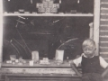 Leo Hedegaard Gravesen, søn af Christian Refstrup Gravesen (1914-1999) og Alma Hedegaard Gravesen (f. Poulsen, 1916-2005), fotograferet foran sin fars købmandsforretning i Vind Stationsby. Omkring 1940. For yderligere oplysninger, se menupunktet 'Vind i billeder' -> 'Månedens billede, marts 2015'.