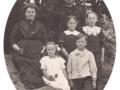 Tømrer og husmand i Virkelyst, Nis Jørgen Hansen (1877-1965) og hustru Inger Marie Hansen (f. Jeppesen, 1875-1955) fotograferet med fire af deres børn. Forrest sidder Magda Theodora Hansen (1907-1958) og Jens Viktor Jeppe Vestergaard Hansen (1905-1999). Bag dem står til venstre Sigrid Dagmar Hansen (1902-1986) og Klara Marie Hansen (g. Pedersen, 1903-1980) til højre. Omkring 1915.