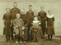 Gårdmand i Skold, Jens Jacobsen (1846-1923) fotograferet med sin hustru Kirsten Marie Jacobsen (f. Lauritsen, 1867-1946) og deres syv børn. Forrest hos forældrene Mads Østergaard Jacobsen (1909-1983) og Ane Marie Jacobsen (g. Haaning, 1914-2008). Stående fra venstre Johanne Jacobsen (g. Nielsen, 1904-1990), Laurits Jacobsen (f. Lauritsen, 1896-1983), Jacob Jacobsen (1899-1936), Kirsten Johanne Kathrine Jacobsen (g. 'Crone' Christensen, 1902-1992) og Mariane Meldgaard Jacobsen (g. Kristensen, 1907-1980). Omkring 1915.