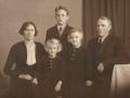 Gårdmand i Øster Skovgård og senere i Røjkærgård, Anders Jensen (1899-1991) og hustru Karen Jensen (f. Troldtoft, 1904-1993) fotograferet med deres tre ældste børn. I baggrunden står Svend Troldtoft Jensen (1928-2010), foran til venstre Edith Troldtoft Jensen (g. Mortensen, 1936-2020) og Margrethe 'Grethe' Troldtoft Jensen (g. Pedersen, 1932-2014) til højre. Omkring 1940.