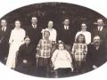 Købmand i Vind Kirkeby, Jens Christian Jensen (1867-1938) og hustru Ane Kathrine Jensen (f. Thomsen, 1869-1947) fotograferet med deres børn omkring 1920. Forrest, mellem forældrene, fra venstre ses Else Lydia Jensen (g. Sønderby, 1911-1996), Helene Kirstine Jensen (1909-1922) og Anna Ingeborg Jensen (1913-1997). I bageste række står fra venstre Jens Arnold Jensen (1902-1991), Dagny Kathrine Jensen (g. Laursen, 1904-1982), Niels Peter Jensen (1893-1970), Mette Marie Jensen (g. Hansen, 1899-1976), Karl Marius Jensen (1897-1988), Karen Marie Jensen (1901-1985) og Mogens Christian Jensen (1895-1969).