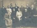 Gårdmand i Røjkær, senere i Øster Skovgård, Mads Jacobsen (1845-1921) fotograferet med sin hustru Ane Marie Sofie Jacobsen (f. Andersen, 1867-1939) og deres ni børn omkring 1920. Siddende forrest til venstre ses Johanne Katrine Marie Kristine Jacobsen (g. 'Kirkeby' Nielsen, f. 1897) og mellem forældrene står Martine Amalie Jacobsen (g. 'Tipsmark' Pedersen, 1908-1998). Stående bagest ses fra venstre Kristen Damgaard Jacobsen (1902-1953), Anine Amalie Jacobsen (1906-1955), Kristian Peder Jacobsen (1892-1961), Mads Sofus Jacobsen (1895-1976), Jens Kristian Jacobsen (1899-1980), Jacob Kristian Jacobsen (1893-1981) og Niels Alexander Damgaard Jacobsen (1904-1987).