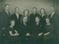 Gårdmand i Sønder Vindgab, Jens Bak Poulsen (1890-1975) og hustru Sigrid Poulsen (f. Søndergaard, 1897-1975) omgivet af deres otte børn. Forrest til venstre Karen Margrethe 'Git' Poulsen (g. Larsen) og Ragnhild Poulsen til højre. Bagest fra venstre Kaj Poulsen (1920-1995), Thomas Søndergaard Poulsen, Inger Marie Poulsen (g. Jensen, 1926-2006), Poul Vindgab Poulsen (1918-1980), Dorrith 'Dot' Elisabeth Poulsen (g. Engelhardt, 1931-1994) og Karl Johan Poulsen (1921-1977). Slutningen af 1950'erne.