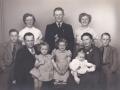 Husmand i Blåbjerghus, Peder Svendsen (1908-1994) fotograferet med sin hustru, Oda Kathrine Svendsen (f. Andersen, 1915-1986) og deres ældste børn. Mellem forældrene fra venstre Signe Kirsten Svendsen (g. Dam), Ellen Elisabeth Svendsen (g. Kruse) og Jytte Margrethe 'Grethe' Svendsen (g. Præstholm) hos sin mor. Stående fra venstre Hans Ejvind Svendsen, Anne Marie Svendsen (g. Hoffmann, 1939-2000), Jens Kristian Svendsen, Inger Kristiane Svendsen (g. Kviesgaard) og Svend Egon Svendsen. Angiveligt 1954. Siden kom også datteren Lilly Solveig Svendsen (g. Falsig) til.