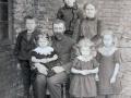 Gårdmand i Troldtoftgård Mourits 'Moust' Troldtoft (f. Jensen, 1870-1951) og hustru Maren Margrethe Troldtoft (f. Jacobsen, 1877-1973) fotograferet med deres børn. Stående bagest Karen Troldtoft (1904-1993), yderst til venstre Niels Valdemar Troldtoft (1906-1980), Eleonora Kirstine Troldtoft (1914-1999) siddende hos sin far, Helga Alvilde Troldtoft (1911-1997) stående foran sin mor og Dagmar Troldtoft (1909-2007) længst til højre. Omkring 1916.