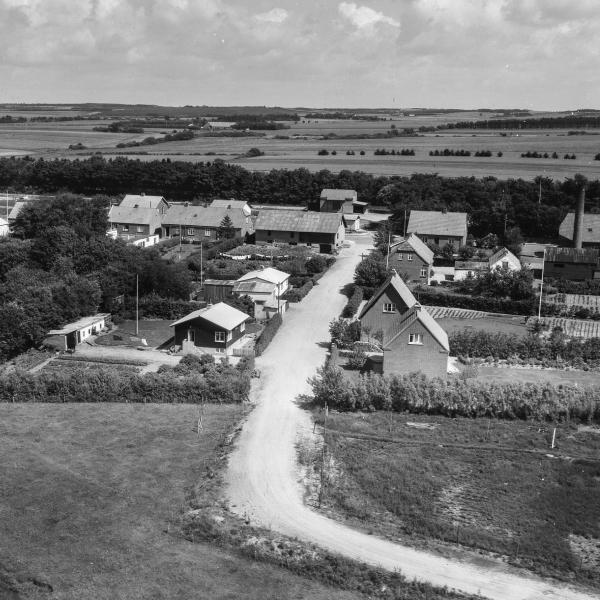 11. Vind by, 1962. Brombærvej set mod Holstebrovej. På hjørnet til venstre Gravesens købmandsforretning. Overfor i baggrunden, foran rækken af træer, jernbanens tidligere pakhus, yderst til højre mejeriets skorsten.
