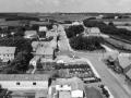 1. Vind by, 1962. Nederst fra højre Ørnhøjvej, der fortsætter som Holstebrovej. Gamle købmand Halkjærs forretning midt i billedet (delvist skjult), dernæst mejeriet. Til højre stationen og den nedlagte bane, bagest den ny-opførte sogne- og hjemmeværnsgård.