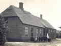 Stråsø Skole -stråtægt skolestue nærmest kameraet og tegltægt lærerbolig i baggrunden. Omkring 1910.