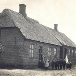 Stråsø Skole -stråtækt skolestue nærmest kameraet og tegltækt lærerbolig i baggrunden. Omkring 1910.