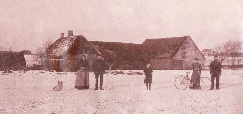 Vester Skovgård fotograferet omkring århundredeskiftet. Stående til venstre med hunden formentlig gårdmand Jens Iversen (f. 1859) og hans hustru Mette Marie Iversen (f. Mohrsen, 1843-1911). Pigen i midten og parret til højre har ikke kunnet identificeres. I baggrunden til højre genkendes tydeligt Vind kirke.