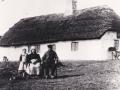 Husmand Lars Boelstoft (1846-1918) og Mette Juline Kirstine Boelstoft (f. Jensen, 1844-1932) fotograferet foran Bakhus, i dag Skjernvej 206, med plejebarnet Mathilde Georgine Christensen (f. 1903). Omkring 1910.