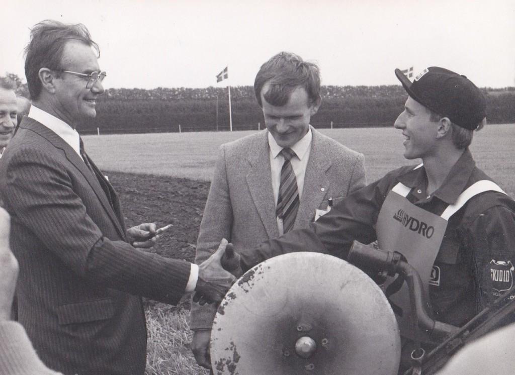 Prins Henrik hilser på 20-årige Lars Gammelvind, yngste deltager ved Verdensmesterskaberne i traktorpløjning i 1985. I midten ses daværende formand for Danmarks Landboungdom, Jens Erik Boesen.