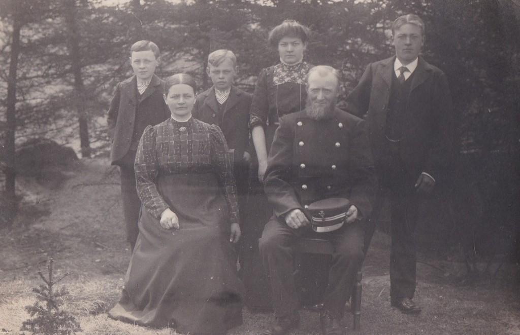 Johannes Mikkelsen (1858-1930) og Ane Marie (f. Kristensen, 1865-1947) fotograferet med fire af deres fem børn omkring 1910. Fra venstre ses Kristian Mikkelsen (1897-1975), Daniel Mikkelsen (1899-1976), Andersine Pouline (g. Bilgrav, 1892-1974) og Mikkel Peder Mikkelsen (1888-1981). Fraværende er datteren Sidsel Siliane (g. Egebjerg, 1894-1969).