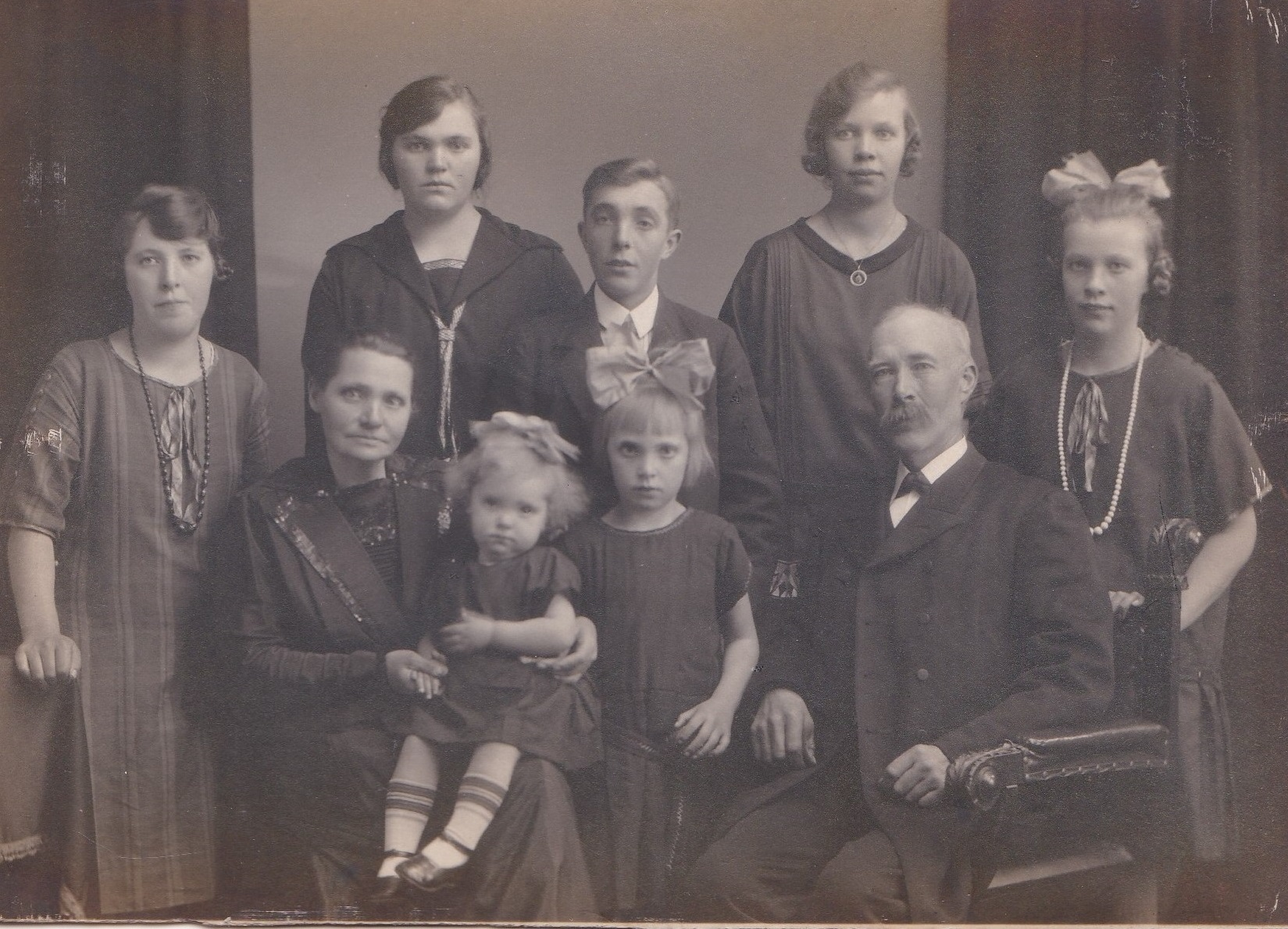 Johannes Nielsen (1871-1950) fotograferet med sin hustru Ane Kirstine (f. Steffensen, 1882-1938) og deres syv børn. Stående fra venstre Edith (g. Bjerregaard, 1911-1984), Anine Kirstine Marie (g. Mikkelsen, 1907-1997), Kristen Arnold Nielsen (1908-1991) og Kirstine Alexandrine (g. Lauritsen, 1910-1952) og Agnes Mary Nielsen (f. 1913). Forrest i midten lille Inga Margrethe Nielsen (f. 1924) og Gerda (g. Poulsen, 1919-1989). Angiveligt 1926.