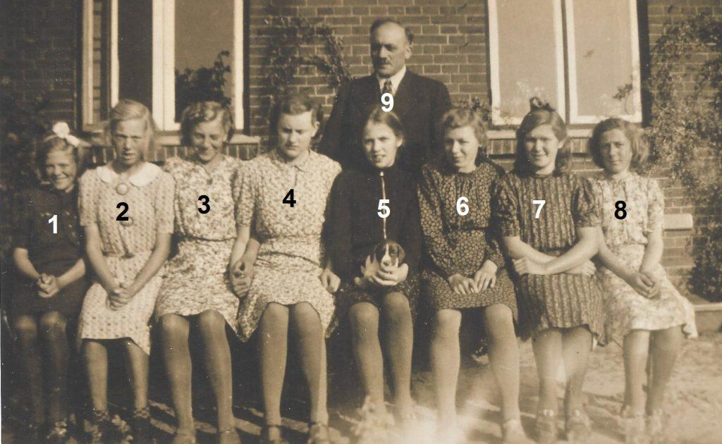 Skoleelever fra Vinding og Vind fotograferet forud for deres konfirmation i efteråret 1941. I alfabetisk rækkefølge: Agnes Ahle, Vind (3), Hilda Jensen, Vind (2), Oda Jensen, Vind (8), Poula Kirstine Jensen, Vinding, Inger Dorthea Lauritsen, Vinding (5), Jenny Krista Lauritsen, Vinding, Anna Lassen, Vinding og Anna Birgitte Kirstine 'Stinne' Nielsen, Vinding (1). Desuden sognepræst Kristian Larsen (9). Skulle nogen kunne være behjælpelig med at oplyse navnene på de uidentificerede konfirmander, hører vi meget gerne herom.