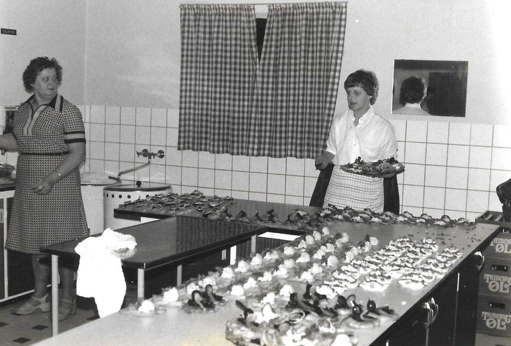 Travlhed i sognegårdens køkken under jubilæumsfesten. Til venstre kogekone fra Sørvad, Astrid Gardsdal (1926-2001) og til højre med serveringsfadet Grethe Stjernholm Jensen (1928-2014), Vind.