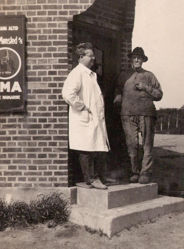 Købmand Halkjær fotograferet på trappen foran sin forretning.