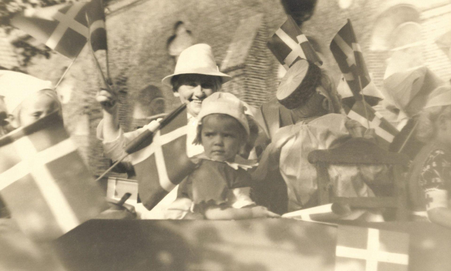 Kristine Kjeldsen (1890-1983), født i Vind og senere mangeårig forstanderinde ved Holstebro Børneasyl, ses siddende i baggrunden med hvid hat omgivet af børn fra asylet. Billedet er efter alt at dømme fra 1940'erne og taget enten i forbindelse med en børnehjælpsdag eller national festdag. I baggrunden genkendes Holstebro Sognekirkes høje mure.