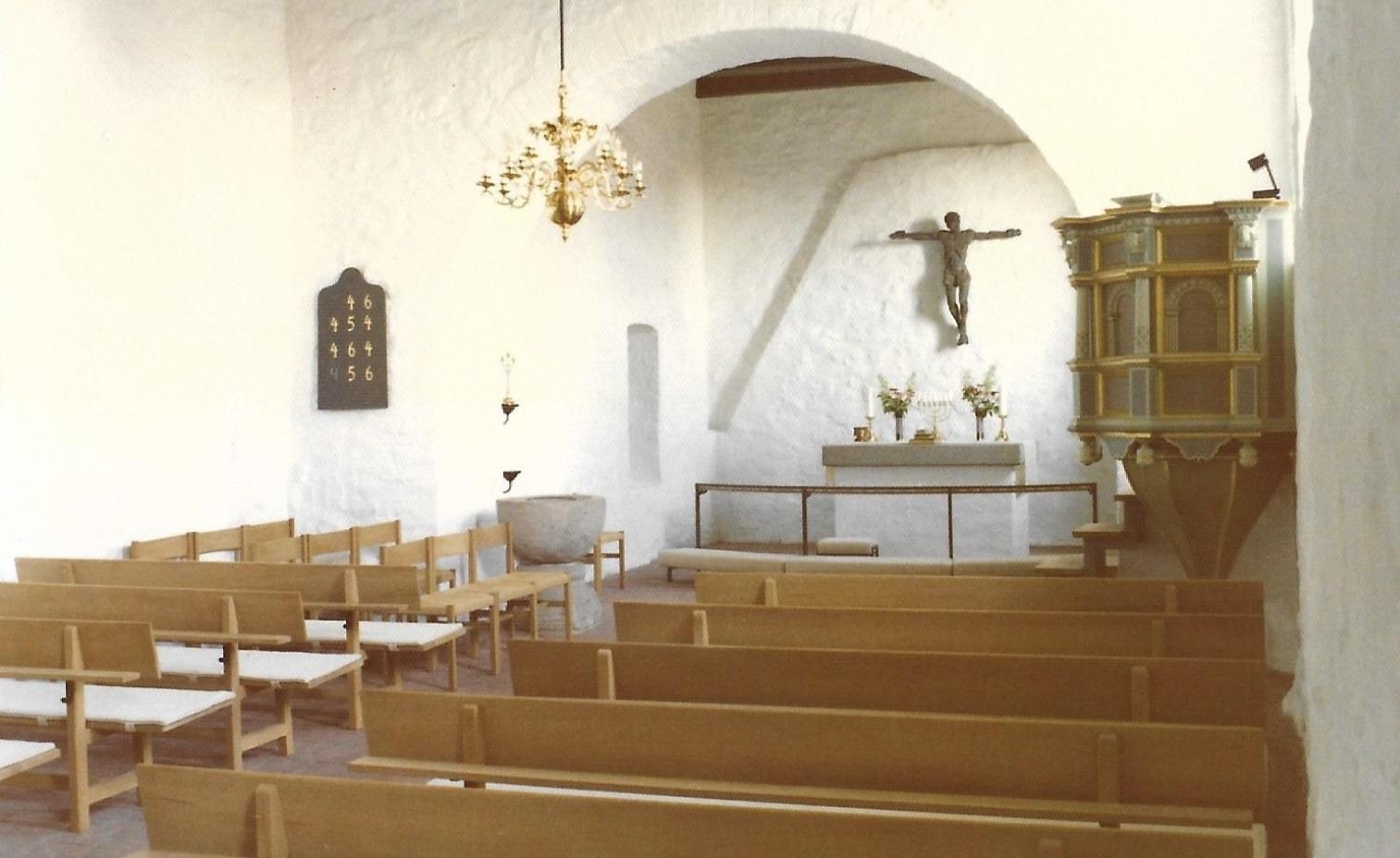 På dette billede af Vind Kirkes indre ses tydeligt egetræsbænkene, der i sin tid blev erhvervet for penge testamenteret af pastor Peter Blicher (1876-1958).