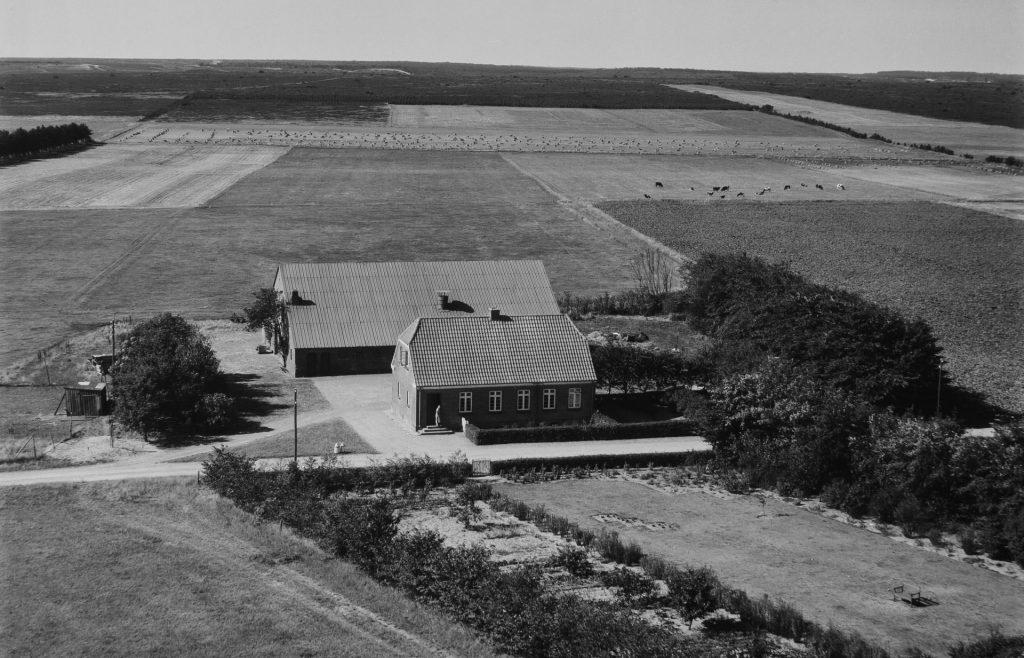 Vesterbo, i dag Råstedvej 7, fotograferet i 1955 med Stråsø i baggrunden. Det må formodes at være Karen Kirkegaard (1903-1964), der ses at stå på indgangstrappen. Bemærk også haven på modsatte side af Råstedvej. Kilde: Det Kongelige Biblioteks Luftbilledsamling.